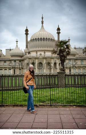 Young woman posing in front of the Brighton Palace Pavilion , a British Royal pleasure palace built in Indo-Saracenic style with ornate onion domes, columns and arches, a popular tourist destination - stock photo