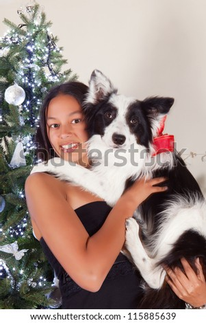Young woman posing in front of the christmas tree with her sheepdog - stock photo