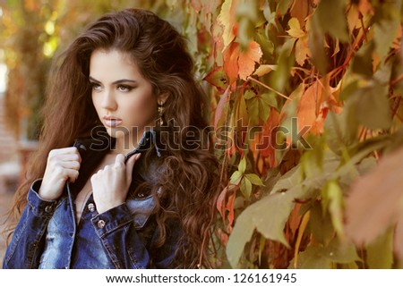 Young woman posing in jacket, outdoors portrait. Soft sunny colors.