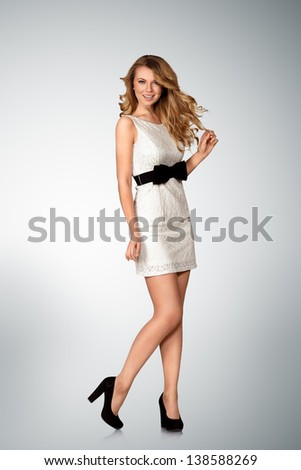 Young woman posing in white mini dress full length portrait - stock photo