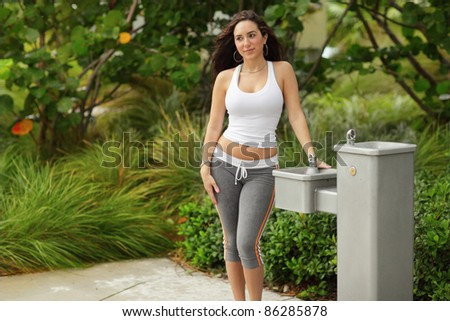 Young woman posing next to a water  fountain - stock photo