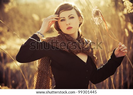 Young woman posing on a field. Focus on face. Sunset. - stock photo