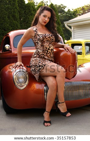 Young woman posing on copper hot rod - stock photo