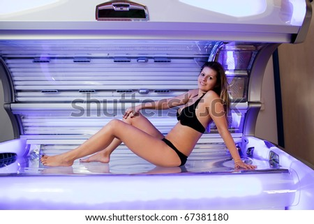 Young woman posing on tanning bed. Indoors solarium shot - stock photo