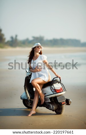 Young woman posing on the beach of the ocean sitting on a scooter. A woman in a white dress looking to the side.