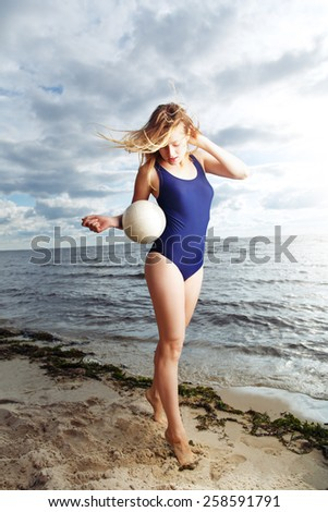 Young woman posing on the beach with volleyball against shore line - stock photo