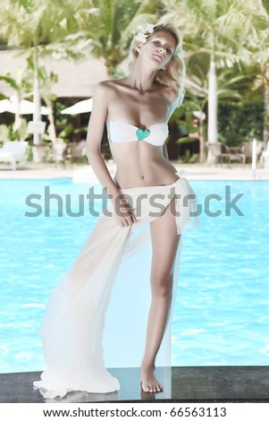 Young woman posing on the edge of swimming pool - stock photo