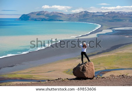 young woman posing on the rock, beautiful Icelandic landscape in the background - stock photo