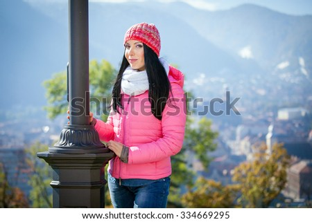 Young woman posing outdoor in autumn. Fashion portrait of pretty girl in cold weather wearing a pink hat and jacket.