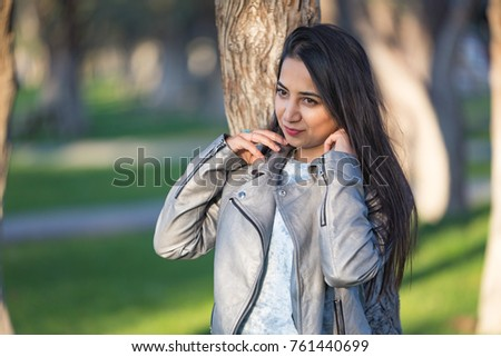 Young woman posing outdoor in the city, having fun in park in the city