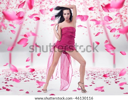 Young woman posing over rose petals background - stock photo