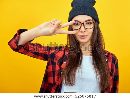 Young woman posing over yellow background. Emotional female portrait. Hipster girl.