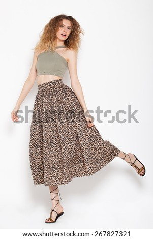 young woman posing relaxed on animal print skirt and green shirt on white background