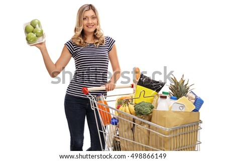 Young woman posing with a pack of apples and a shopping cart full of groceries isolated on white background