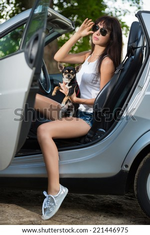 Young woman posing with a pet in grey cabriolet - stock photo