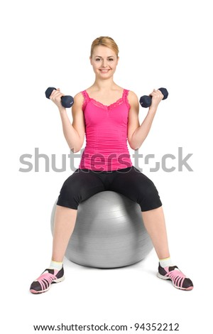 young woman posing with dumbbells sitting on fitness ball, on white background - stock photo