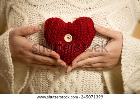 Young woman posing with red heart on white sweater