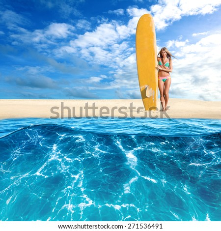 Young woman posing with surfboard on tropical island. View from sea water - stock photo