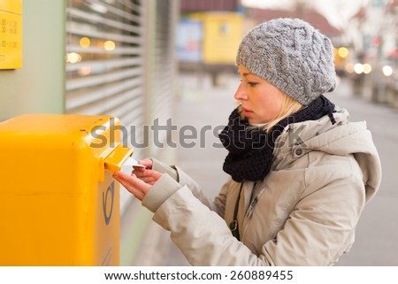 Young woman posting a letter, dropping an envelope in a postbox. - stock photo