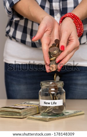 Young woman pouring coins into a jar. She is saving money to start a new life. - stock photo