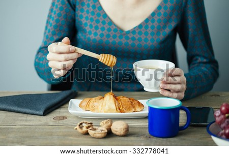 young woman pouring honey on Croissant for breakfast on wooden table - stock photo