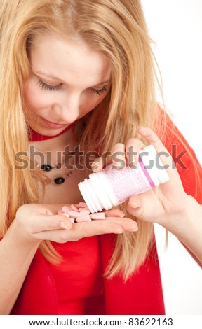 young woman pouring out tablets, drugs, on palm - stock photo