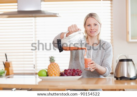 Young woman pouring smoothie into a glass - stock photo