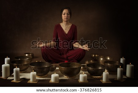 Young woman  practice meditation with Tibetan singing bowls in front of brown background - stock photo