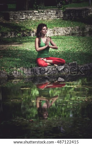 young woman practice yoga outdoor in front pond,  lotus position