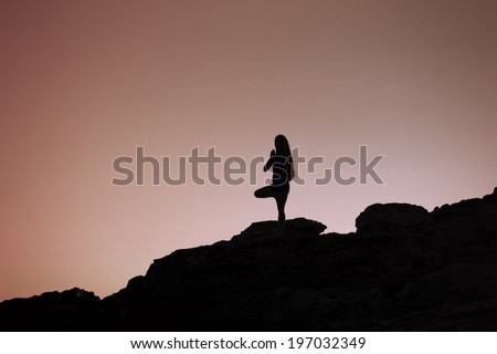 Young woman practices yoga at sunrise - stock photo