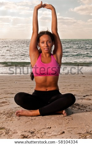 Young woman practices yoga early morning in the beach. - stock photo