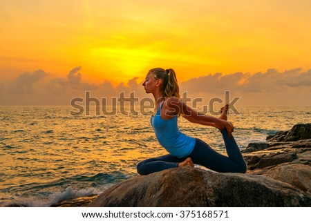 Young woman practices yoga on the rocks against the sea