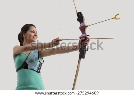 Young woman practicing archery isolated over gray background