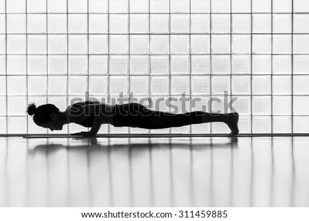Young woman practicing in a yoga studio. Plank pose during sun salutations. - stock photo