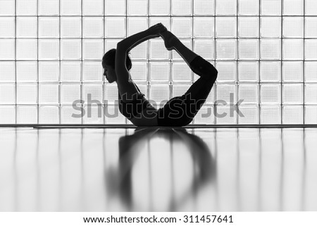 Young woman practicing in a yoga studio. This pose is called bow pose or dhanurasana. - stock photo