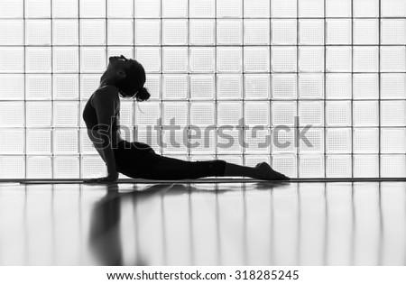 Young woman practicing in a yoga studio. Upward facing dog during sun salutations. - stock photo