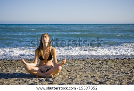 Young woman practicing meditation at the beach in casual clothing - stock photo