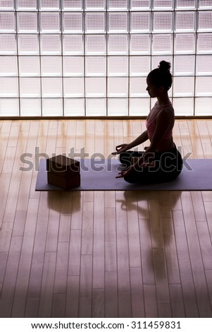 Young woman practicing meditation in a yoga studio indoors. - stock photo