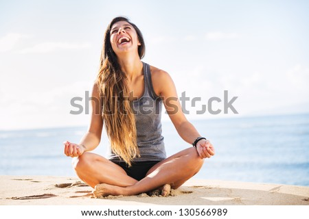 Young woman practicing morning meditation in nature at the beach - stock photo