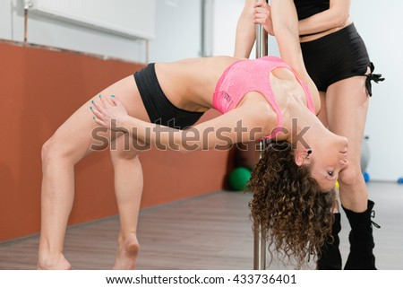 Young woman practicing pole fitness with instructor