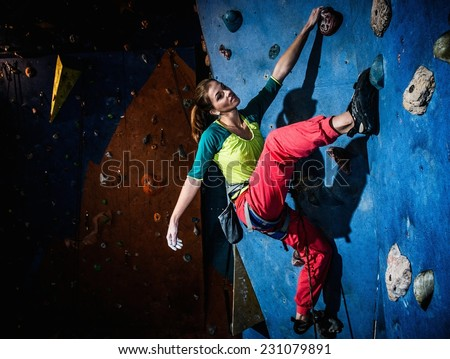 Young woman practicing rock-climbing on a rock wall indoors - stock photo