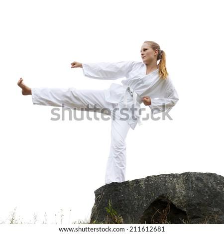 young woman practicing taekwondo kick - stock photo