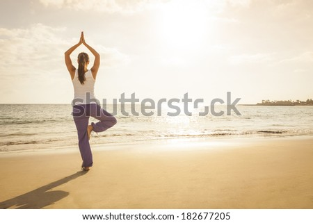 Young woman practicing tree yoga pose near the ocean during sunset - stock photo