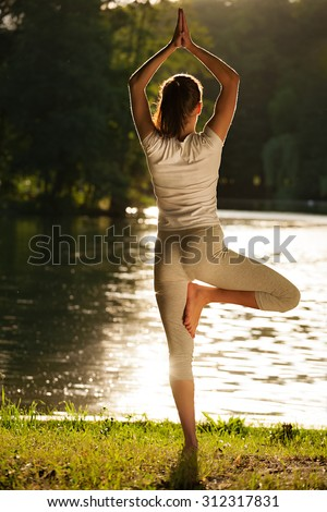 Young woman practicing tree yoga pose near the river during sunset or sunrise. Vrikshasana tree pose from beautiful yoga girl. Caucasian fit model meditating on grass in park  tree pose, vrksasana. - stock photo