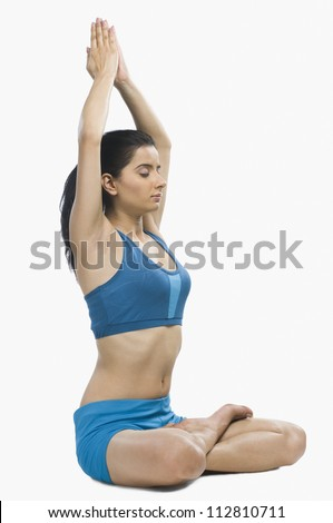 Young woman practicing yoga against white background