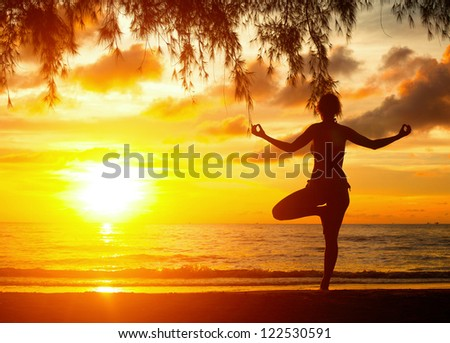 Young woman practicing yoga at sunset on the coast of Thailand