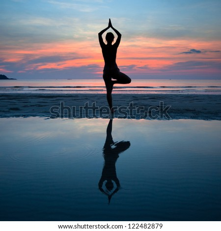 Young woman practicing yoga at sunset on the coast, with the reflection in the water - stock photo