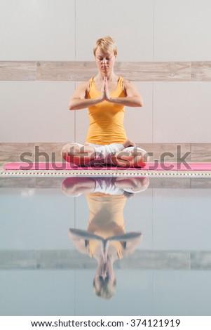 Young woman practicing yoga at swimming pool, Padmasana / Half Lotus Position - stock photo