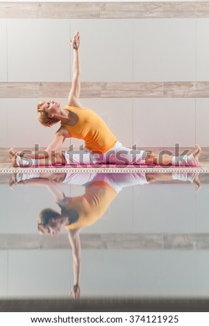 Young woman practicing yoga at swimming pool, Upavistha Konasana / Revolved Seated Angle Pose - stock photo
