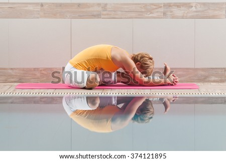 Young woman practicing yoga at swimming pool, variation of Paschimottanasana / Sitting Forward Bend pose - stock photo